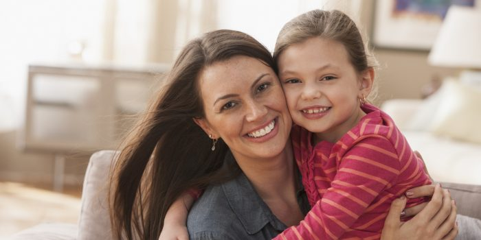 Caucasian mother and daughter hugging on sofa